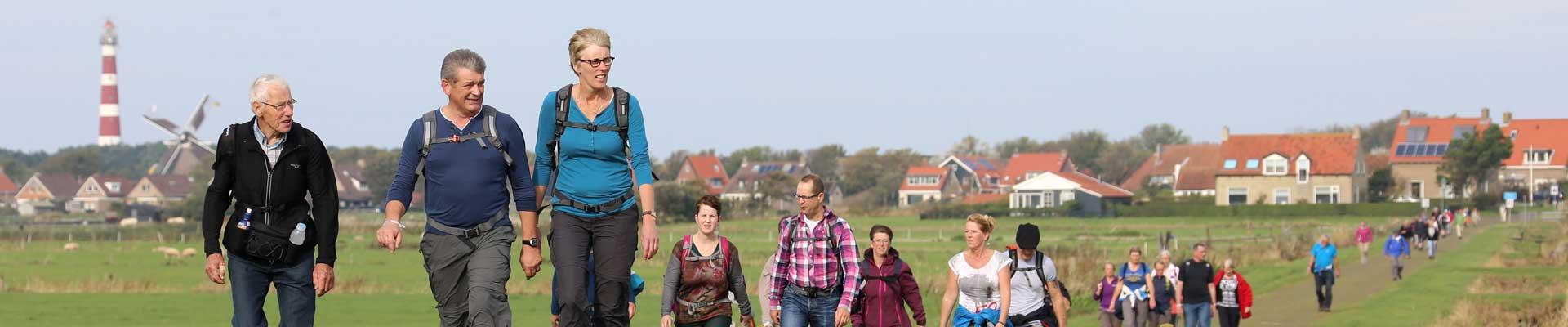 Tussen Slik en Zand: Deelnemers lopen door de velden op Ameland met Hollum en de vuurtoren op de achtergrond