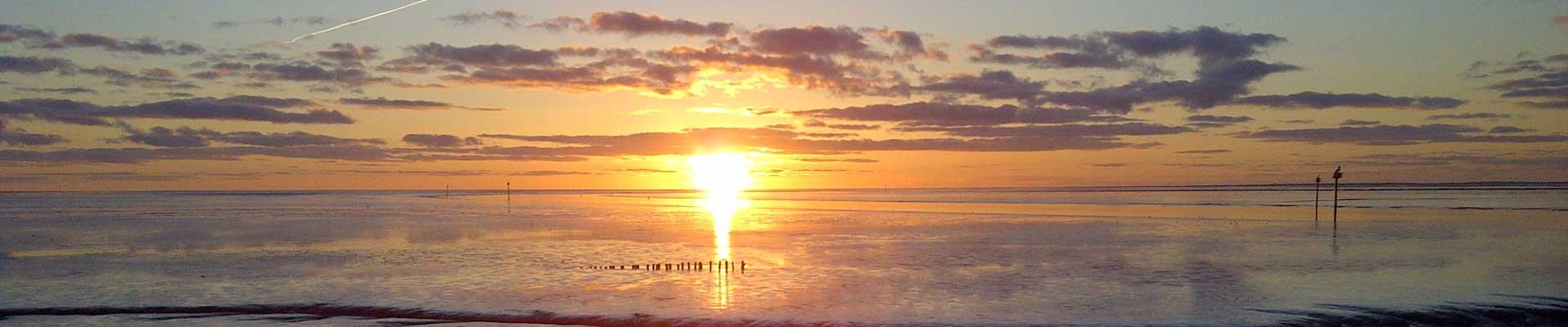 Tussen Slik en Zand: Zicht op de Waddenzee met ondergaande zon